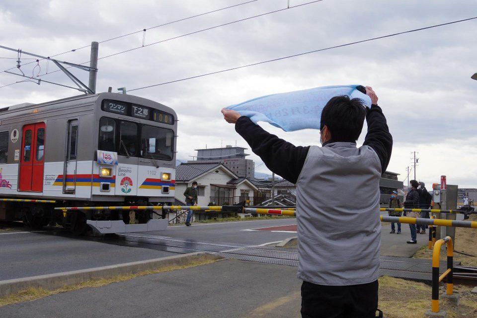 復旧区間を走る電車を祝う人々