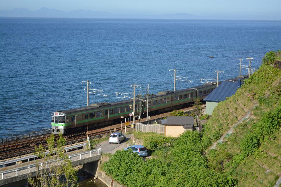 小樽近郊の石狩湾沿いを行くJR北海道の電車